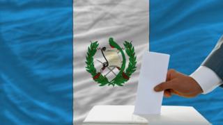 Urna con bandera de Guatemala y hombre votando