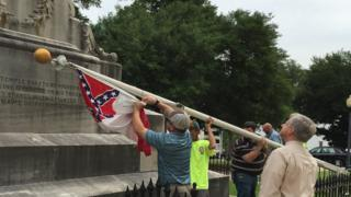 State workers take down a Confederate national flag on the grounds of the state Capitol, Wednesday, June 24, 2015, in Montgomery, Ala.