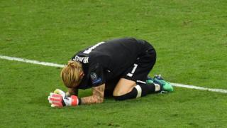 Liverpool goalkeeper Loris Karius drops to his knees on the pitch.