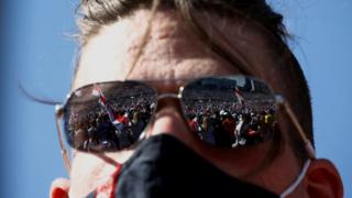 Demonstrators are reflected in the sunglasses of a participant during a protest against the presidential election results
