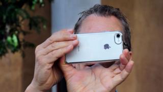 Hombre tomando foto con un iPhone
