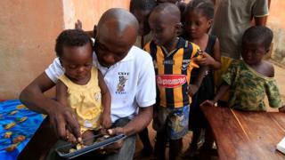 Un père montre à son bébé comment utiliser une tablette