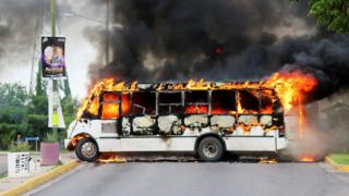 A burning bus set alight by cartel gunmen to block a road