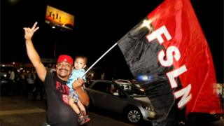 A supporter of Nicaragua's President Daniel Ortega and vice presidential candidate, his wife, Rosario Murillo, holds up a flag of the Sandinista National Liberation Front, or FSLN, while celebrating after preliminary results showed Ortega was on course for re-election, in Managua, Nicaragua November 6, 2016.