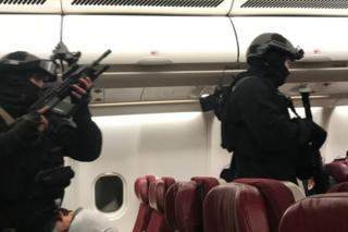 Heavily armed police enter the plane after it returned to Melbourne Airport