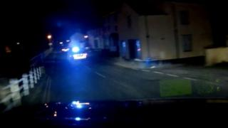 Two police cars with flashing blue lights chase Tyler Wilson's car