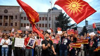 Demonstrators wave flags in front of the parliament building in Skopje on June 23, 2018 during a protest against the new name of the country, the Republic of North Macedonia.