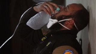 A civil defence member breathes through an oxygen mask, after what rescue workers described as a suspected gas attack in the town of Khan Sheikhoun