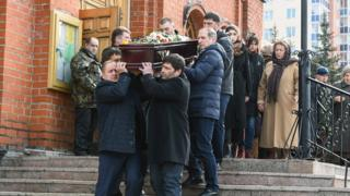 Men carry the coffin of a victim of a shopping mall fire out of a church during a funeral service in the industrial city of Kemerovo in western Siberia on March 28, 2018. Russia on March 28, 2018
