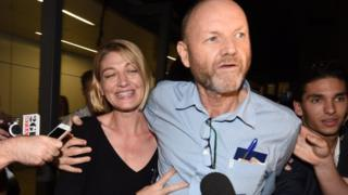Stephen Rice with his arm around Tara Brown, in an airport, pushing through a crowd of people with microphones