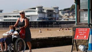 Two women pass a coronavirus warning sign at Western-super-Mare