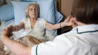 A woman lying in bed holding the hands of a carer