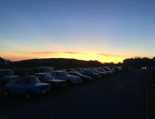 Sunset over a field with cars in
