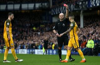 Anthony Knockaert of Brighton and Hove Albion is shown a red card by referee