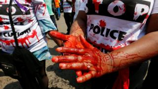 """A member of the civil society smears her hands with mock blood as others chant slogans, during a protest dubbed """"Stop extrajudicial killings"""" on the killing of human rights lawyer, Willie Kimani, his client and their driver in Nairobi, Kenya, July 4"""