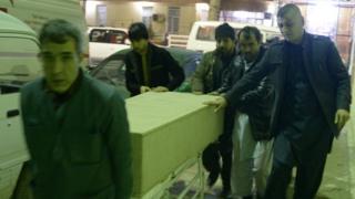 Men unload coffin of an ICRC employee killed by gunmen in Jowzjan province at a hospital in Mazar-i-Sharif, Afghanistan February 8, 2017