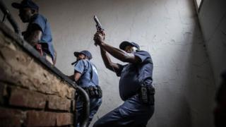 South Africa police officers, one pointing a gun, raid a building in Pretoria, South Africa - Friday 24 February 2017