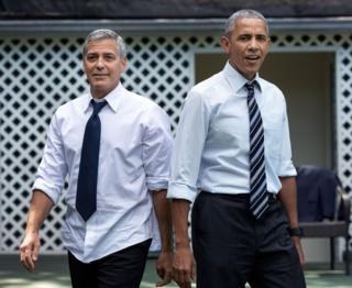 George Clooney, left, and Barack Obama, right, stand back-to-back with shirtsleeves rolled up and top buttons undone.