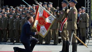 Polish President Andrzej Duda kneels before a military flag before taking over authority Polish Armed Forces as the Polish Armed forces during the ceremony at Pilsudski Square in Warsaw, Poland