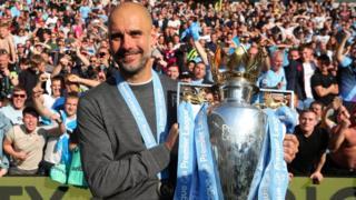 Manchester City boss Pep Guardiola holds the Premier League trophy