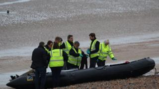 National Crime Agency officers examine a boat at Greatstone beach in Kent that arrived carrying 12 migrants on 31 December 2018