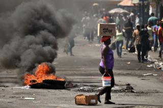 A tire placed by a small group of demonstrators burns on a street in the commune of Petion Ville in the Haitan capital Port-au-Prince