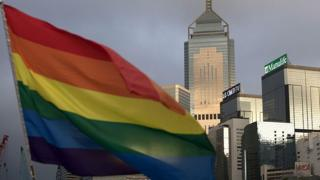 A rainbow flag, a symbol of the Lesbian, Gay, Bi-sexual and Transgender (LGBT) community is seen in front of the city skyline in Hong Kong on November 6, 2015.