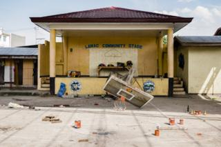 A basketball hoop and backboard lies broken in front of the Lamac Community Stage in the Visayan Region of the Philippines