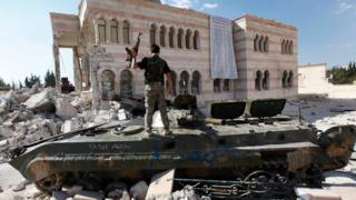 A Free Syrian Army soldier stands on a damaged Syrian military tank in front of a damaged mosque, which were destroyed during fighting with government forces