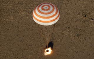 A capsule with a parachute lands in the desert