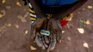 """An FGM """"cutter"""" in Kenya shows the razorblade she uses to cut girls' genitals"""