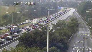 Traffic is queuing on the eastbound carriageway at Llandarcy
