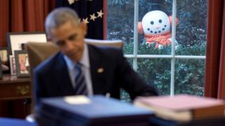 An out-of-focus Mr Obama works at this desk. Visible in the window, in sharp focus, is an elaborate snowman with scarf and earmuffs.