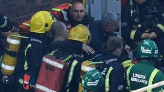 A man is rescued from the fire by fire fighters and paramedics