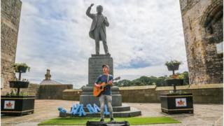 Cerddor yn canu dan gerflun Lloyd George ar faes Caernarfon