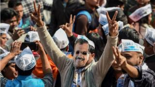 An Aam Aadmi Party (AAP) supporter wears a mask of party chief Arvind Kejriwal while celebrating with others at the party headquarters in New Delhi on February 11, 2020