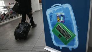 L'affiche d'un ordinateur portable dans le hall d'un aéroport, avec un voyageur au second plan