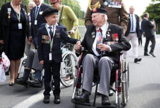D-Day veteran John Quinn holds hands with George Sayer