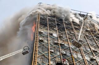 Iranian firefighters attempt to control fire at the Plasco building in Tehran, Iran