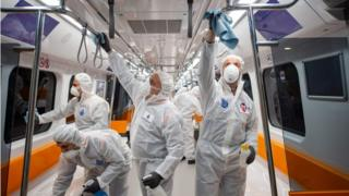 Employees of the Istanbul Municipality wearing protective gear disinfects a subway carriage 12 March 2020