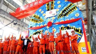 Trabalhadores chineses próximos a uma das super máquinas que estão sendo usadas em projetos de infraestrutura dentro e fora do país