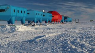 Halley research station in the foreground. The sky is bright blue