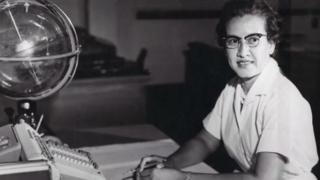 Katherine Johnson sits on a sphere