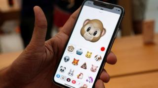 "A man holds up new iPhone with ""animoji"" feature"