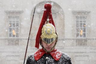 A Household Cavalry Guard stands in the blizzard as heavy snow hits Westminster