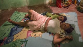 Diego cuddles his Grandma on a Winnie the Pooh blanket on the floor
