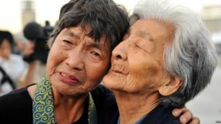 Tsuyuko Nakao (R), 92, and Kinuyo Ikegami, 77, survivors of the atomic bombing, comforting each other after offering prayers for victims