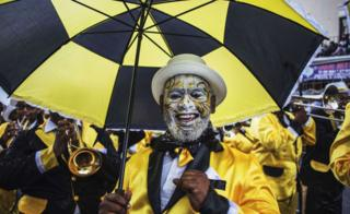 A man with face paint and matching black-and-yellow umbrella
