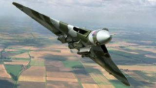 Vulcan bomber flying in the air over countryside