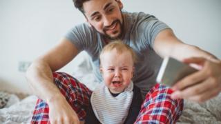 Un padre se hace un selfie con su hijo llorando.